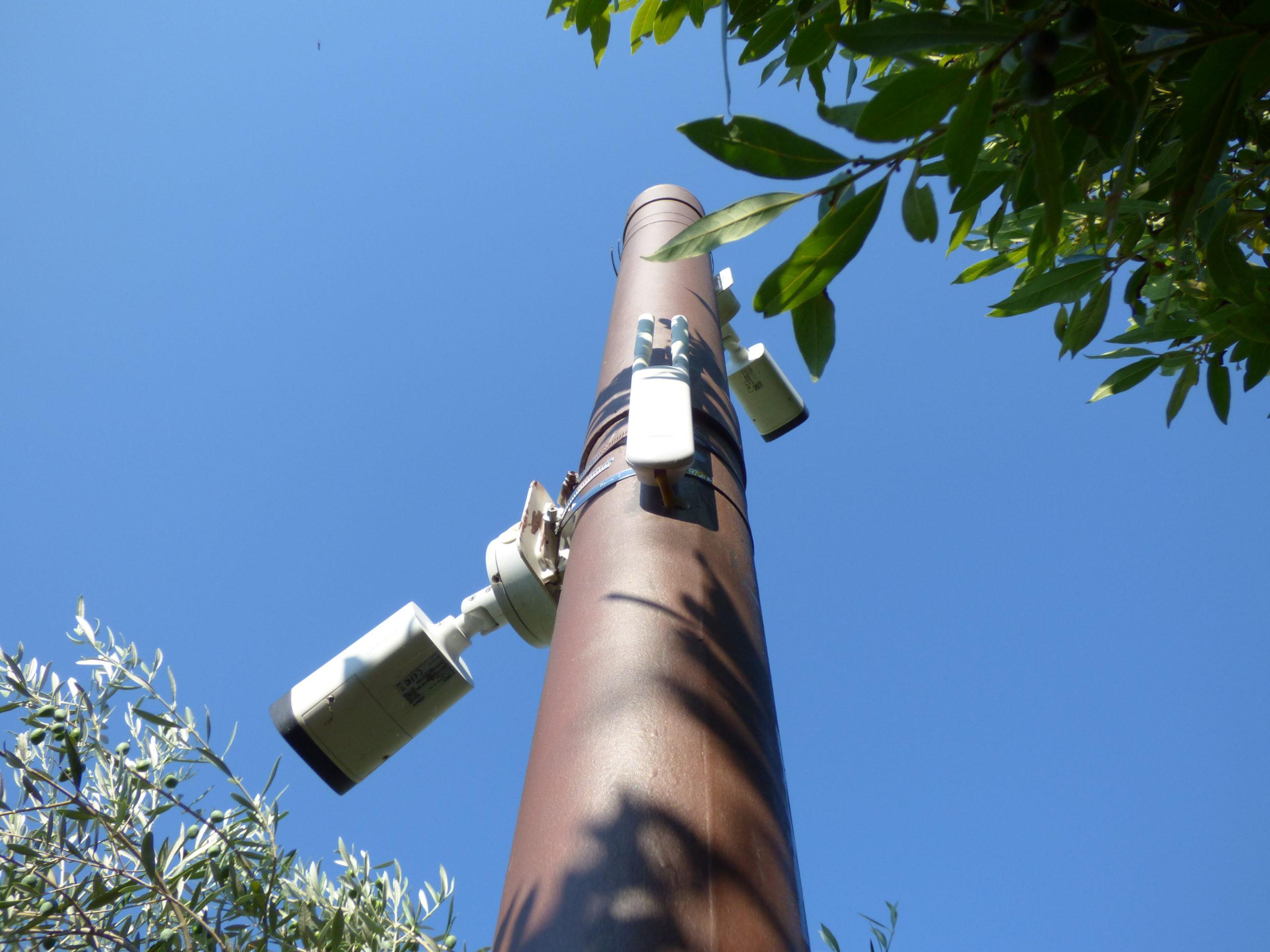 Caméra de vidéosurveillance tube sur un poteau surveillant les extérieurs d'une villa. Il y a aussi une borne wifi pour capter internet dans le jardin.